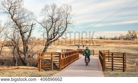 mature male cyclist and walkers on a newly constructed bike trail in a typical winter or fall scenery without snow in Fort Collins in northern Colorado