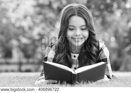 Reading Only Enhances Your Knowledge. Happy Child Read Book Lying On Green Grass. School Library. Im