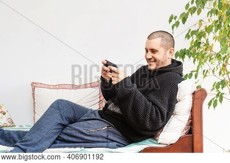 Relaxed Young Caucasic Man In Comfortable Clothes Lying On Comfortable Couch, Playing With Her Frien