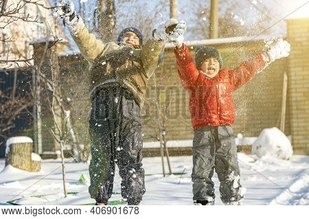 Two Boys Play With Snow. Happy Childhood. Brothers On A Walk. Two Kids Playing With Snow. Toned