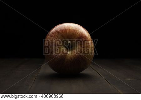 Still Life Image Of One Organic Gala Apple Close Up On Rustic Wooden Surface And Black Background