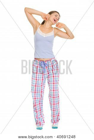 Full Length Portrait Of Young Woman In Pajamas Stretching And Ya