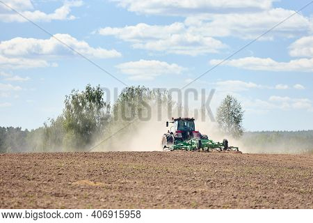 Typical Agricultural Scene Tractor Cultivation In Field In Clouds Of Dust Drives Off Into The Distan