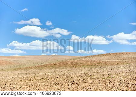 Ploughed Arable Plowing Agricultural Land Plowed For Crops Under Blue Sky With Clouds Conceptual Bac