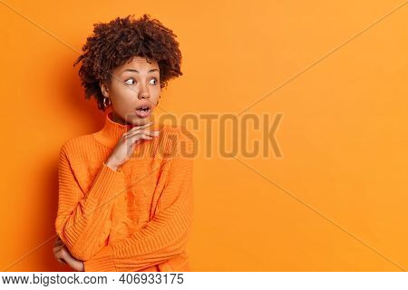 Studio Shot Of Stupefied African American Woman Holds Chin And Stares Aside Dressed In Casual Orange