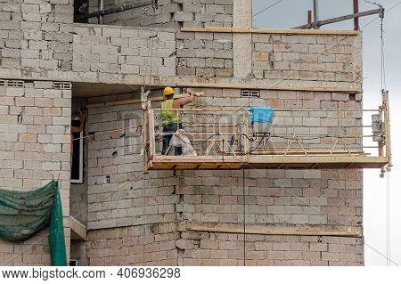 Construction Worker At Lifting Platform Works Outside The Cinder Block Building. Batumi, Georgia