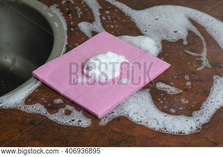 A Pink Viscose Dishcloth On The Kitchen Table With Foam. Cleaning, Dishwashing, Household Chores. Cl