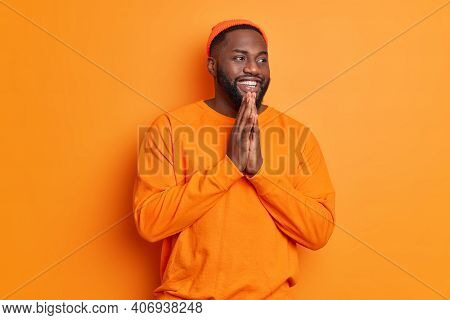Positive Dark Skinned Bearded Man Smiles Happily Keeps Palms Together Has Belief In Better Wears Cas