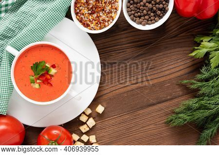 Delicious Cream Soup Of Tomatoes On A Wooden Background With Herbs And Croutons. In A Soup Bowl.
