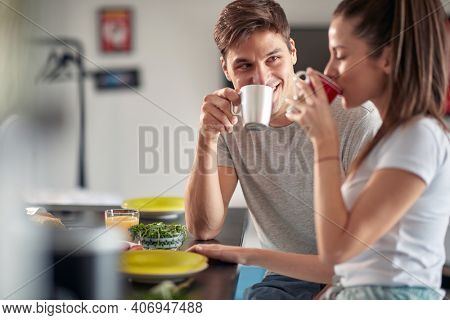 A young couple drinking a coffee before breakfast in a relaxed atmosphere at home. Couple, relationship, breakfast, together