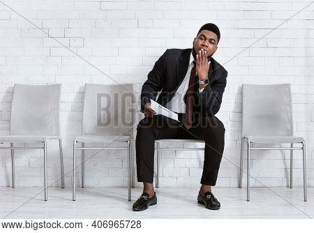 Headhunting And Personnel Recruiting. Bored Black Guy With Cv Yawning, Tired Of Waiting For His Job