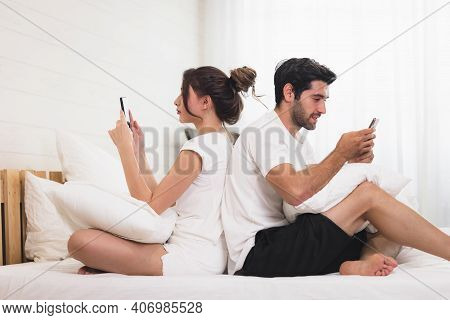 Millennial Couple In Quarrel, Lying In Bed Back To Back, Using Cellphones