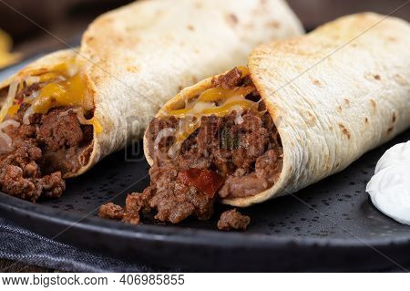 Closeup Of Two Burritos With Ground Beef, Refried Beans And Cheese On A Black Plate