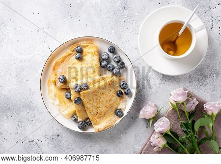 Flat Lay Composition With Beautiful Breakfast. Delicious Thin Pancakes, Cup Of Tea And Bouquet Of Ro