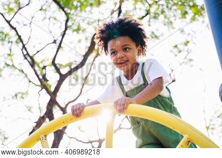 Cute African American Little Kid Boy Having Fun While Playing On The Playground In The Daytime In Su