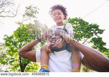 African American Father Giving Son Ride On Back At Park. Family Playing Togetherness And Relaxes. Fa