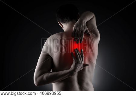 Pain Between The Shoulder Blades, Man Suffering From Backache On Black Background