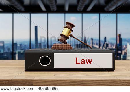 Judge Gavel Standing On Black Office Binder File Folder On Wooden Desk In Large Office Building; Wit
