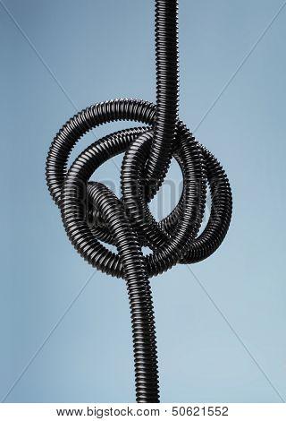 Tangled black flexible air hose.