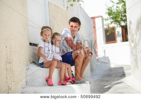 Young Father And Cute Daughters Sitting On Doorstep Old House At Street In Emporio, Santorini
