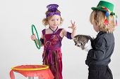Two children in costumes of magicians show a trick with a kitten, focus on girl poster