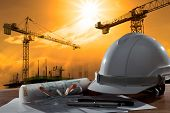 file of safety helmet and architect pland on wood table with sunset scene and building construction poster