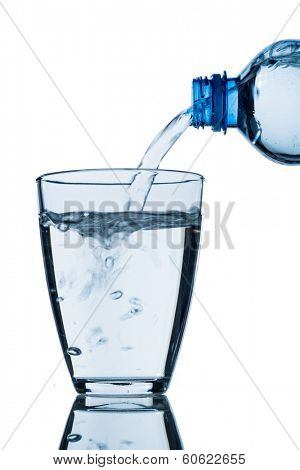 from a bottle of water being poured into a glass, symbol photo for drinking water demand and consumption