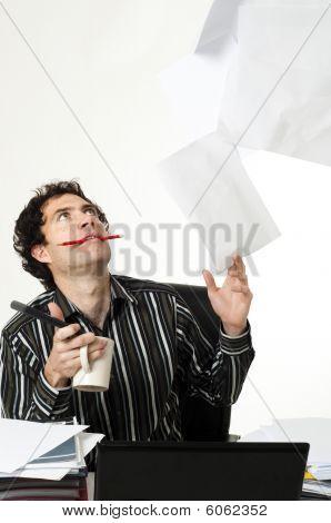 Man Sitting At Desk Throwing Up Paperwork