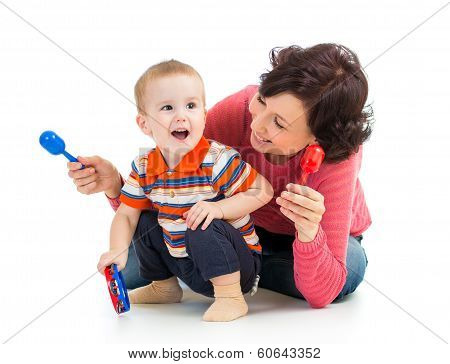 Mother And Baby Boy Having Fun With Musical Toys. Isolated On White Background