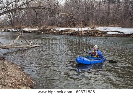 senior male paddling a packraft (one-person light raft used for expedition or adventure racing) on the Cache la Poudre River in Fort Collins, Colorado, winter or early spring
