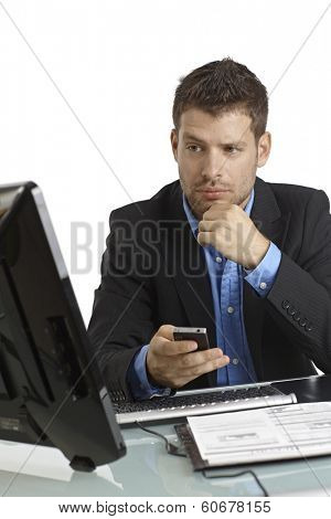 Young businessman sitting at desk, looking at screen, starting phone call.