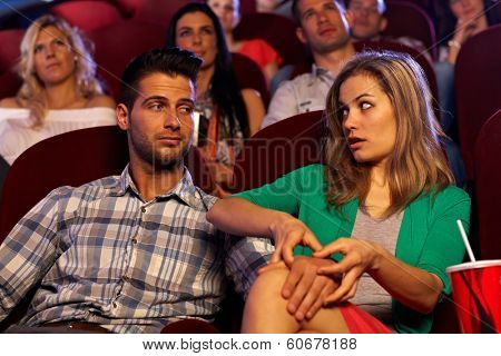 Young man molesting pretty girl in cinema, touching leg.