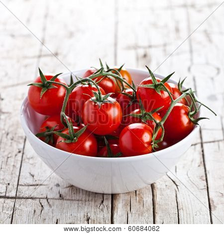 fresh cherry tomatoes in a bowl on rustic wooden background