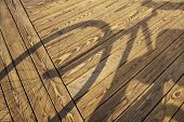 Shadow cast by bicyclist on the boardwalk. poster
