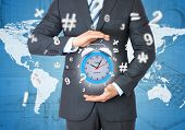 Man in suit holding alarm clock in hand. The concept of time poster