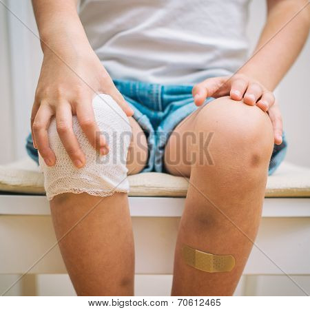 Child Knee With Adhesive Bandage, Bruise And Gauze Bandage.