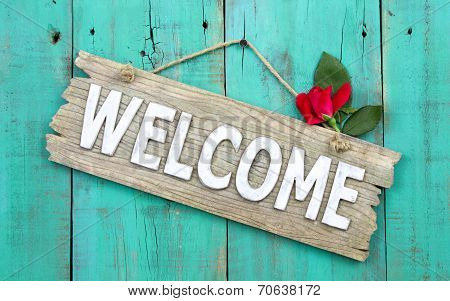 Weathered welcome sign with red rose bud hanging on antique green wood door
