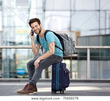 Young Man Sitting On Suitcase And Calling By Cellphone