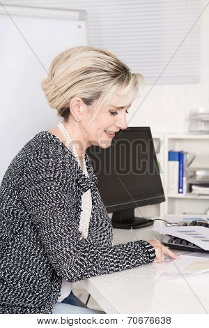 Senior Female Worker Sitting At Desk Looking At Business Paper.