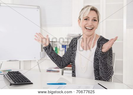 Satisfied And Cheering Business Woman Sitting At Desk.
