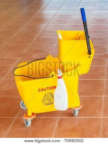 Mop Bucket And Wringer With Caution Sign On The Floor