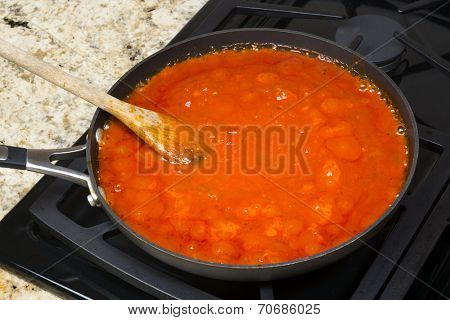 Fresh marinara spaghetti sauce with spices simmering on a gas stove before being added to the pasta.