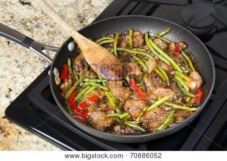 Fresh Asian style beef stir fry with green beans, peppers, onions in teriaki marinara sauce cooking in a saute pan on a stove top.