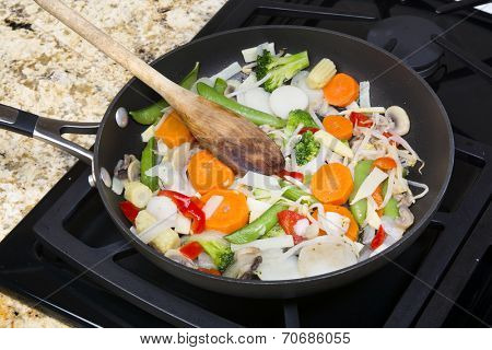 Fresh mixed vegetable stir fry with onions, carrots, snow peas, red peppers, and sprouts simmering in a stovetop frying pan.