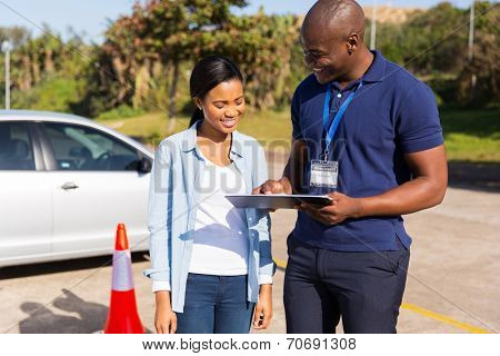 african learner driver with instructor before talking driving test