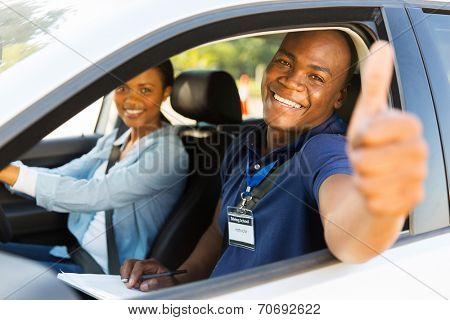 happy male african driving instructor in a car with learner driver giving thumb up