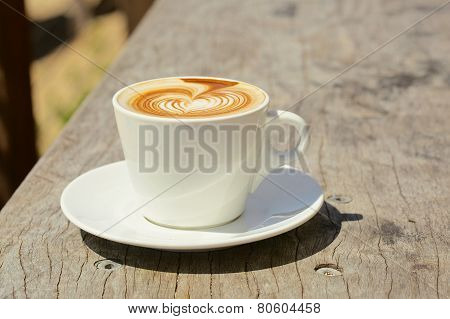 Cappuchino or latte coffe in a white cup with heart shaped foam