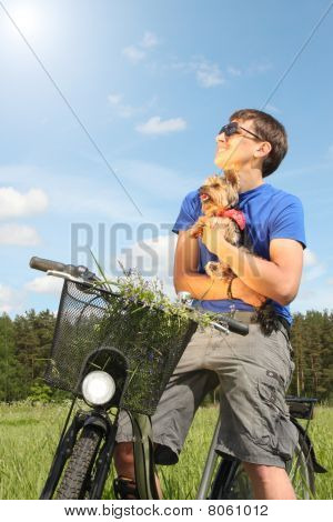 Young handsome man riding a bike in the middle of meadow and holding his dog