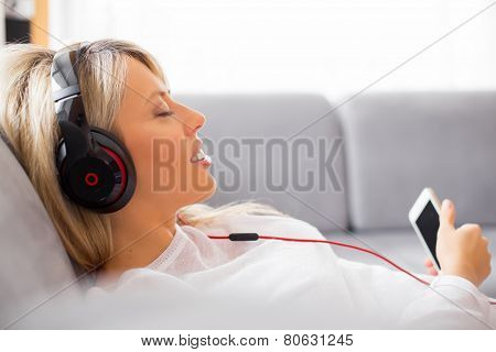 Relaxed woman listening to music on headphones