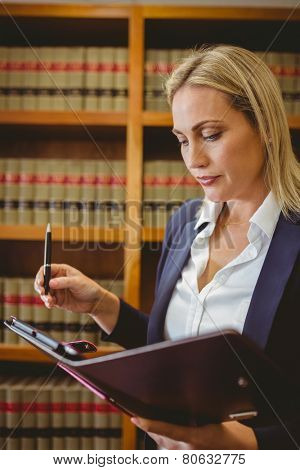 Focused female librarian holding textbook in library